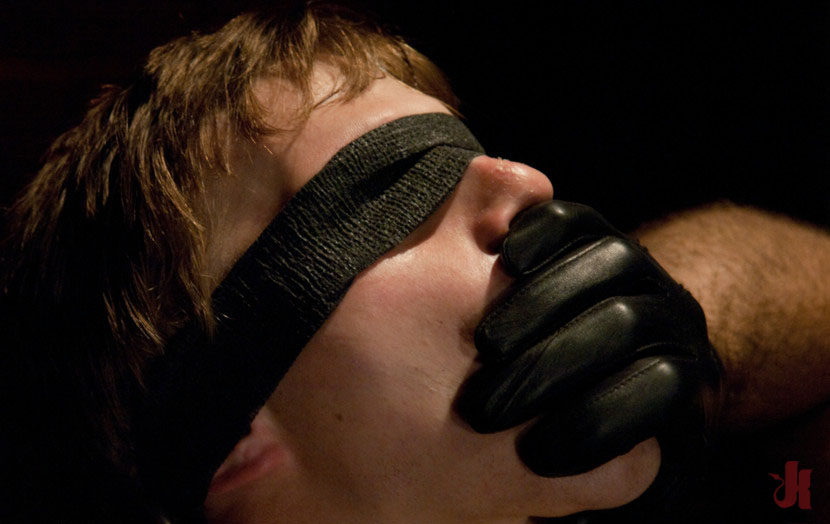 Submissive gay man is blindfolded, tied up and has his mouth covered by a ...
