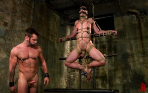 Blindfolded and gagged gay man has his balls stretched with some weights and his nipples clamped