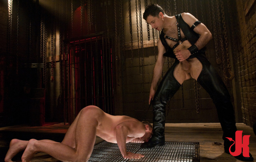 Gay slave licks Master's leather boot in a dungeon full of chains
