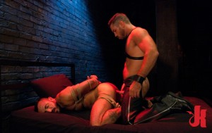 Tied up, submissive man gets fucked in the ass doggy-style in a dim light by his Master