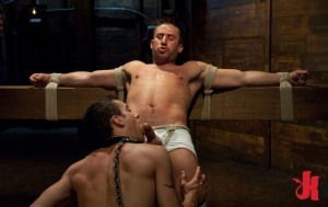 Collared and chained slave licks another mans cock that is tied down to a wooden block