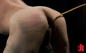 Submissive, gay slave gets his ass caned while bent over and waits to get ass-fucked