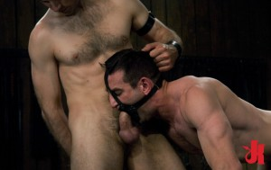 Gay, male slave with a mouth stretcher gets throat-fucked by his dominant partner