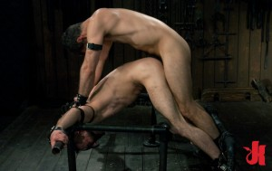 Dominant man fucks his submissive, gay slave while he is bound in leather and cuffed