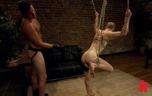 Tied up, gay man with his leg up in the air gets flogged while Master jerks off his own dick